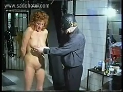 Milf slave got large needles in her ass and breast by masked master in a dungeon