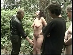 Milf slave tied to a tree gets spanked on her legs and hit on her pussy by master