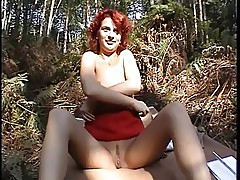 Redhead slut gets naked in the wood